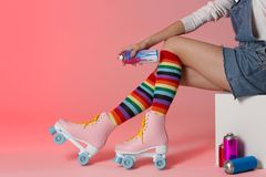 Woman with vintage roller skates and spray paint cans on color background. Closeup stock photo