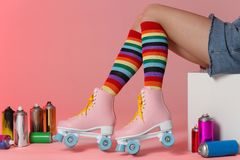 Woman with vintage roller skates and spray paint cans on color background. Closeup royalty free stock photo