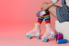 Woman with vintage roller skates and spray paint cans. On color background, closeup. Space for text stock photos