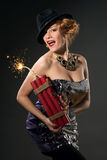 Woman in vintage style dress and hat holding dynamite Royalty Free Stock Photography
