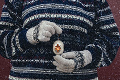 Woman in vintage sweater holding Christmas decorations in her hands in snowfall Stock Photography
