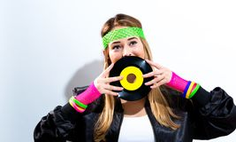 Woman with a vinyl record in 1980`s fashion. On a white background stock images