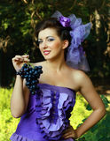 Woman in violet fashion dress  grapes Royalty Free Stock Photos