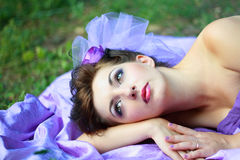 Woman in violet fashion dress laying Royalty Free Stock Image