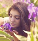 Woman with violet flowers in spring garden Stock Photography