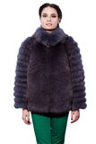 Woman in a violet fur coat made of arctic fox and green pants Stock Image