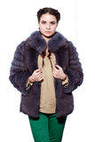 Woman in a violet fur coat made of arctic fox and green pants Royalty Free Stock Photos