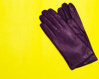 Woman violet leather gloves on yellow background top view flat lay Stock Photos