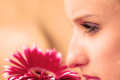 Woman with violet make-up and flower Stock Photography