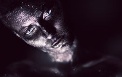 Woman in violet paint and glitter. In studio Royalty Free Stock Images