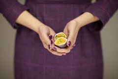 Woman in violett 50`s dress hands holding some passion fruits. Sensual studio shot can be used as background stock images