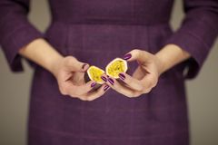 Woman in violett 50`s dress hands holding some passion fruits. Sensual studio shot can be used as background stock photo