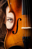 Woman with violin. In dark room Stock Image