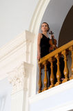 Woman with violin on balcony. Attractive young woman in stunning black dress holding violin and bow on balcony of concert hall Stock Photo