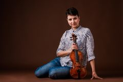 Woman with violin. Beautiful woman with violin on dark brown background Stock Photography