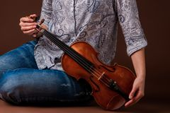 Woman with violin. Beautiful woman with violin on dark brown background Royalty Free Stock Photo