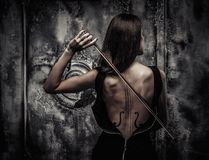 Woman with violin body art. Woman in dress with violin body art holding bow Royalty Free Stock Photo
