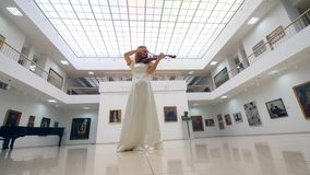 Woman with a violin performs in a museum room alone. 4K stock video footage