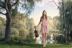 Woman with Violin Standing Near the Lake Stock Photos