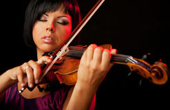 Woman violinist. Beautiful woman is playing a violin on black backround stock photography
