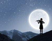 Woman violinist. Silhouette of woman playing violin at night Royalty Free Stock Photography
