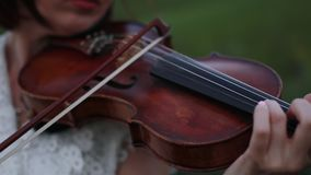 Woman violinist plays the violin on meadow at dusk. stock footage