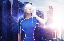 Woman in virtual reality glasses over space city Stock Images