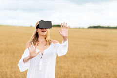 Woman in virtual reality headset on cereal field. Augmented reality, gaming, summer holidays, technology and people concept - happy young woman with virtual Stock Images