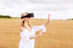 Woman in virtual reality headset on cereal field. Augmented reality, gaming, summer holidays, technology and people concept - happy young woman with virtual Royalty Free Stock Photo