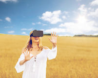 Woman in virtual reality headset on cereal field. Augmented reality, gaming, summer holidays, technology and people concept - happy young woman with virtual Stock Photos