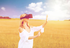 Woman in virtual reality headset on cereal field. Augmented reality, gaming, summer holidays, technology and people concept - happy young woman with virtual Royalty Free Stock Images