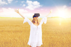 Woman in virtual reality headset on cereal field. Augmented reality, gaming, summer holidays, technology and people concept - happy young woman with virtual Royalty Free Stock Photography