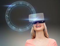Woman in virtual reality headset or 3d glasses. Technology, augmented reality, astrology, horoscope and people concept - happy young woman in virtual headset or Royalty Free Stock Photography