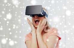 Woman in virtual reality headset or 3d glasses. Technology, augmented reality, cyberspace, entertainment and people concept - happy amazed young woman with Stock Images