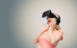 Woman in virtual reality headset or 3d glasses. Technology, virtual reality, entertainment and people concept - happy young woman with virtual reality headset or Royalty Free Stock Photos