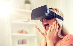 Woman in virtual reality headset or 3d glasses. Technology, virtual reality, cyberspace, entertainment and people concept - happy amazed young woman with virtual Stock Image