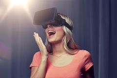 Woman in virtual reality headset or 3d glasses. Technology, virtual reality, cyberspace, entertainment and people concept - happy amazed young woman with virtual Royalty Free Stock Images