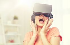 Woman in virtual reality headset or 3d glasses. Technology, virtual reality, cyberspace, entertainment and people concept - happy amazed young woman in virtual Stock Images