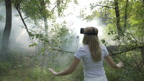 Woman with virtual reality headset goggles following vr ghost girl in smoke in the forest -. Woman with virtual reality headset goggles following vr ghost girl stock footage