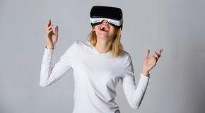 Woman with virtual reality headset. Portrait of an amazed girl using a virtual reality headset on grey royalty free stock image