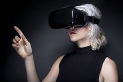 Woman with Virtual Reality Headset Touching Something. Woman wearing a virtual reality headset touching or holding something.  She is interacting with something Royalty Free Stock Image