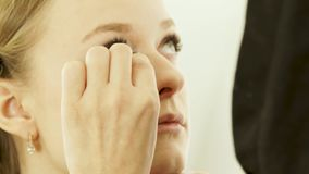 Woman visagiste using cosmetics sponge for make up face young woman in beauty studio. Close up young woman model during. Makeup face in beauty school stock footage
