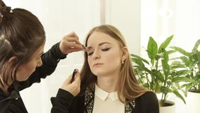 Woman visagiste using cosmetics sponge for makeup correction on face beautiful woman in dressing room. Close up makeup. Woman face in beauty studio stock video footage