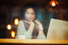 Woman visionary in cafe at laptop. Young beautiful woman visionary in cafe at laptop Royalty Free Stock Image
