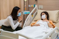 Free Woman Visiting And Take Care Female Patient On Bed At Hospital. People Must Be Wearing Medical Mask To Prevention Coronavirus Stock Photo - 186064180