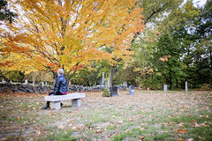 Woman visiting grave in cemetery. A back view of an elderly woman sitting on a bench in a cemetery stock photography