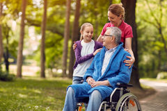 Woman visiting her disabled father in wheelchair with granddaugh Stock Photo