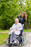 Woman is visiting her grandmother. Young women is visiting her grandmother in nursing home having a walk with here in a wheelchair Stock Image