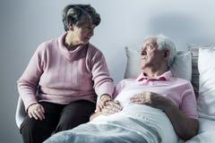 Woman visiting man at hospice. Image of helpful women visiting old men at hospice stock photo