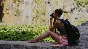 Woman taking photo in Plitvice Lakes National Park. Woman visiting Plitvice Lakes National Park stock video footage